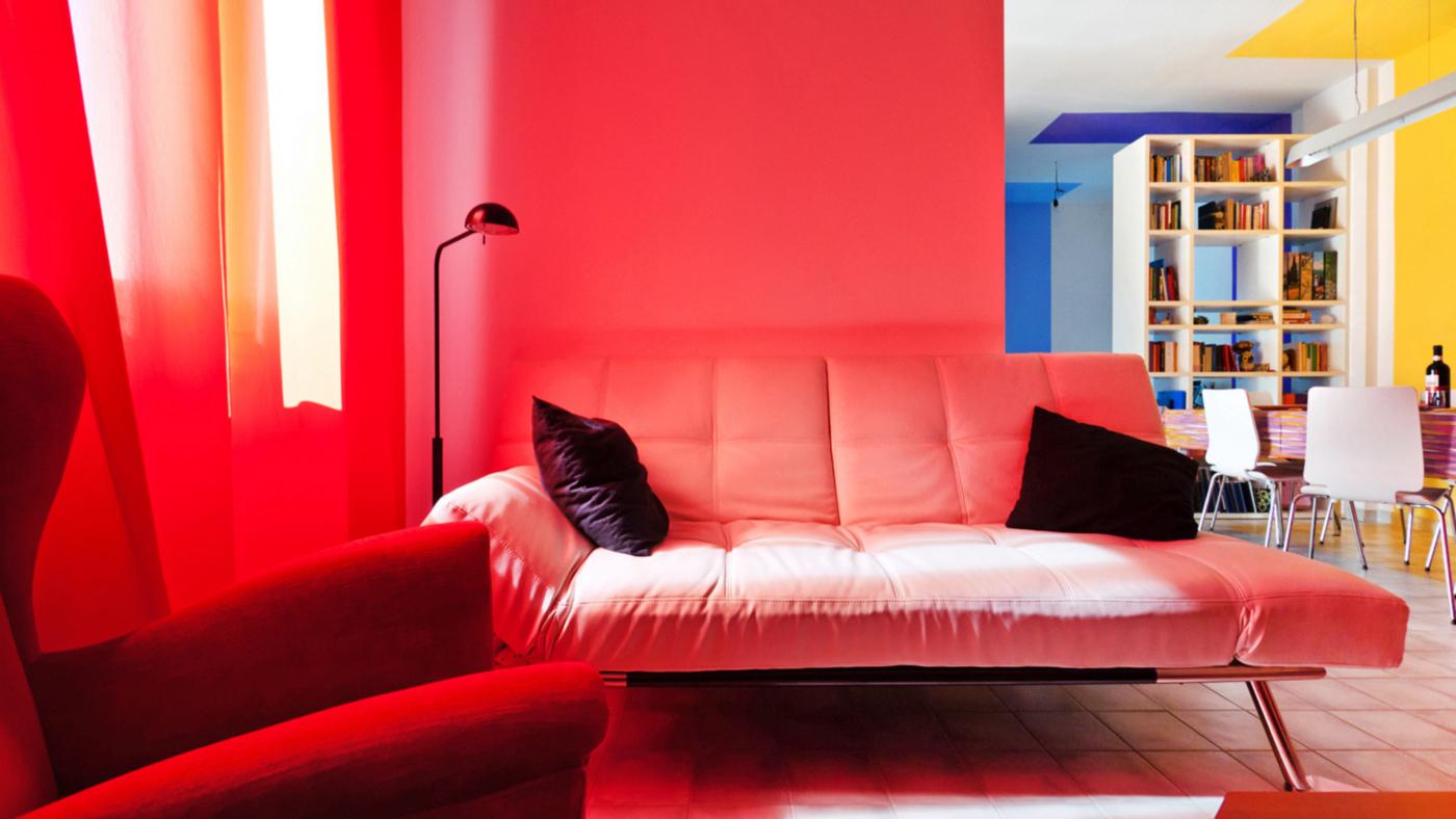 Una ristrutturazione che trasforma il colore in spazio. La zona salotto viene colorata dalle tende in un rosso che crea un perenne tramonto | Bottega di Architettura