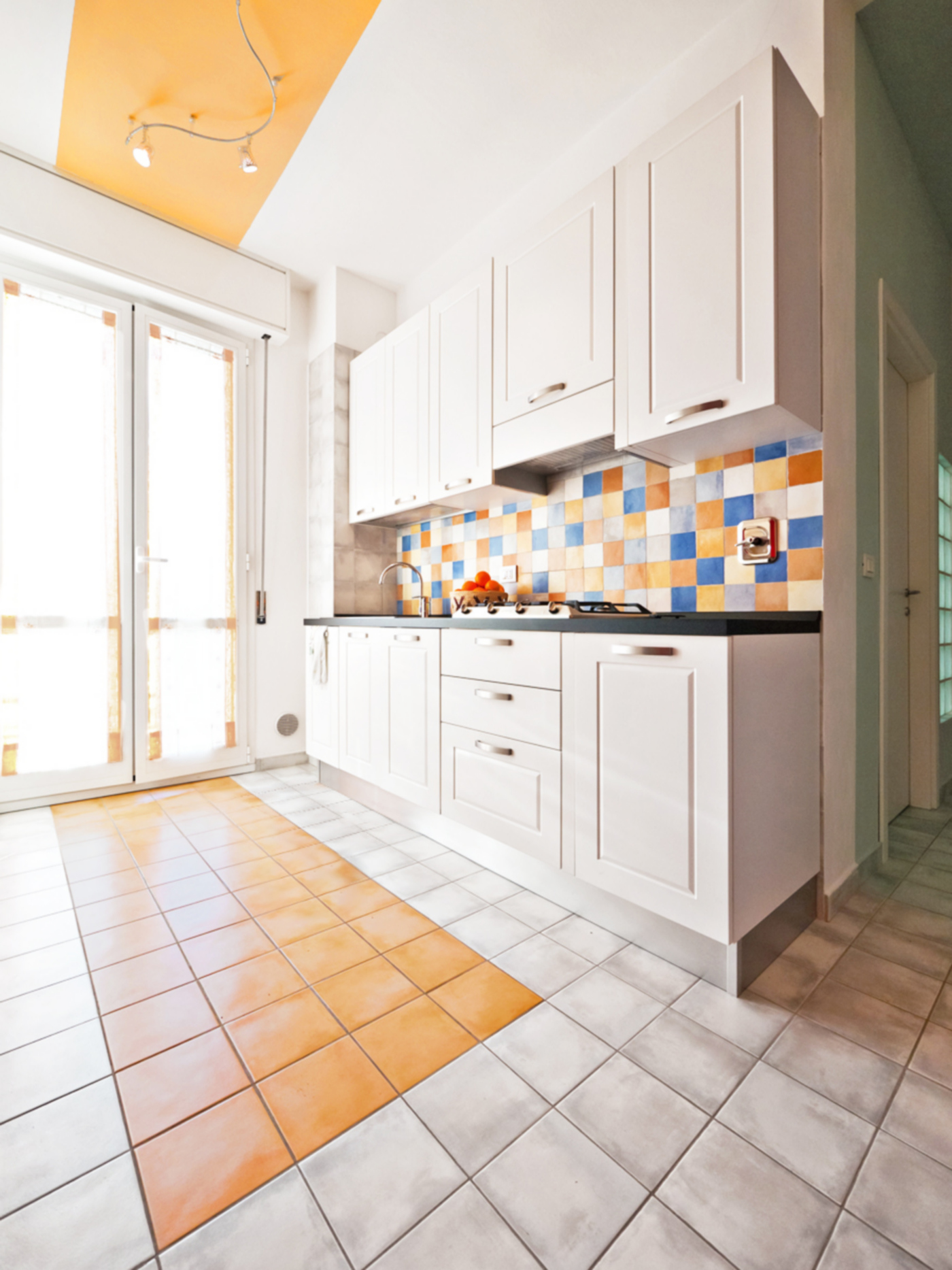 Una ristrutturazione che trasforma il colore in spazio. La cucina arreda la nicchia arancione | Bottega di Architettura