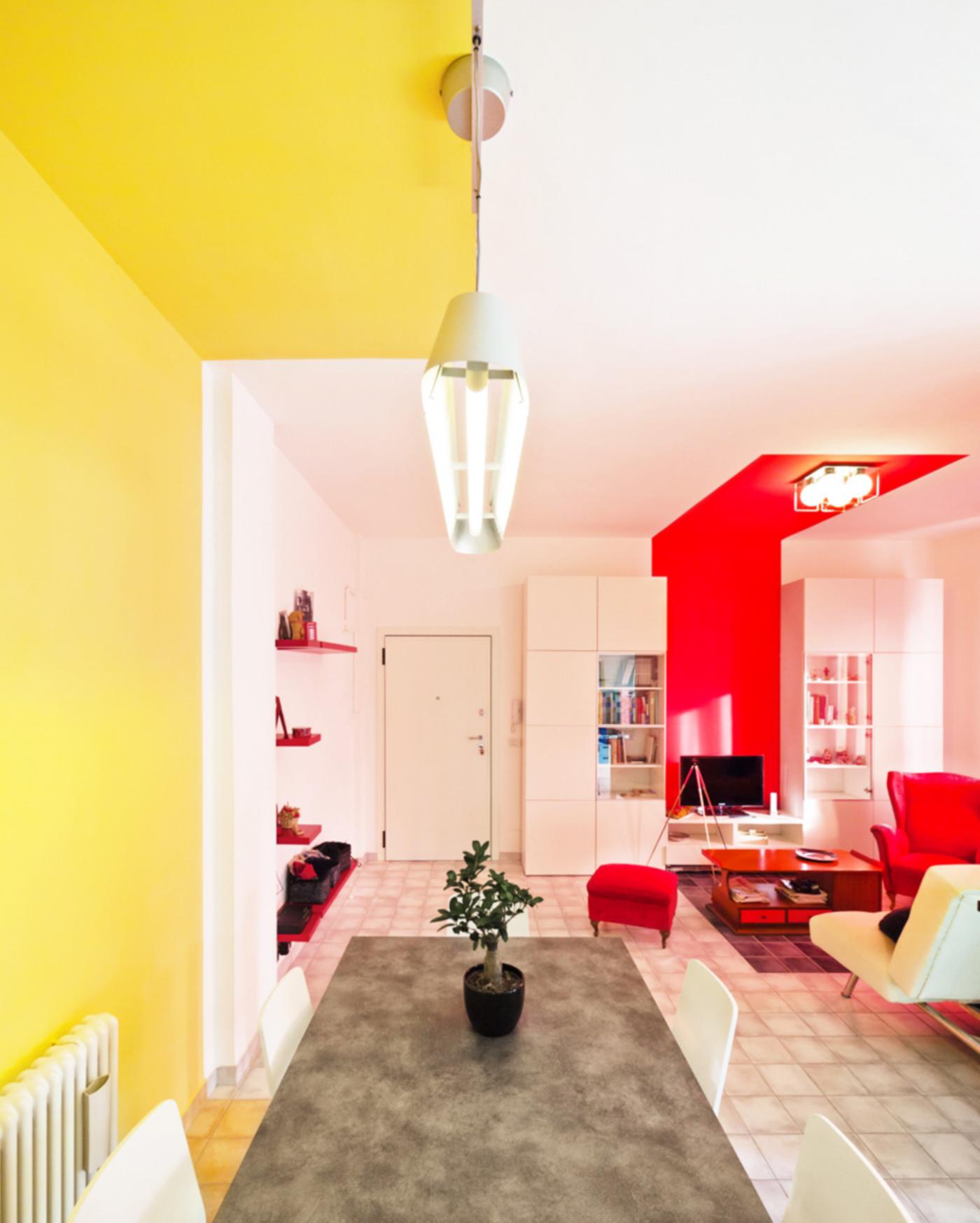 Una ristrutturazione che trasforma il colore in spazio. Il limite della zona gialla, sul grande tavolo | Bottega di Architettura