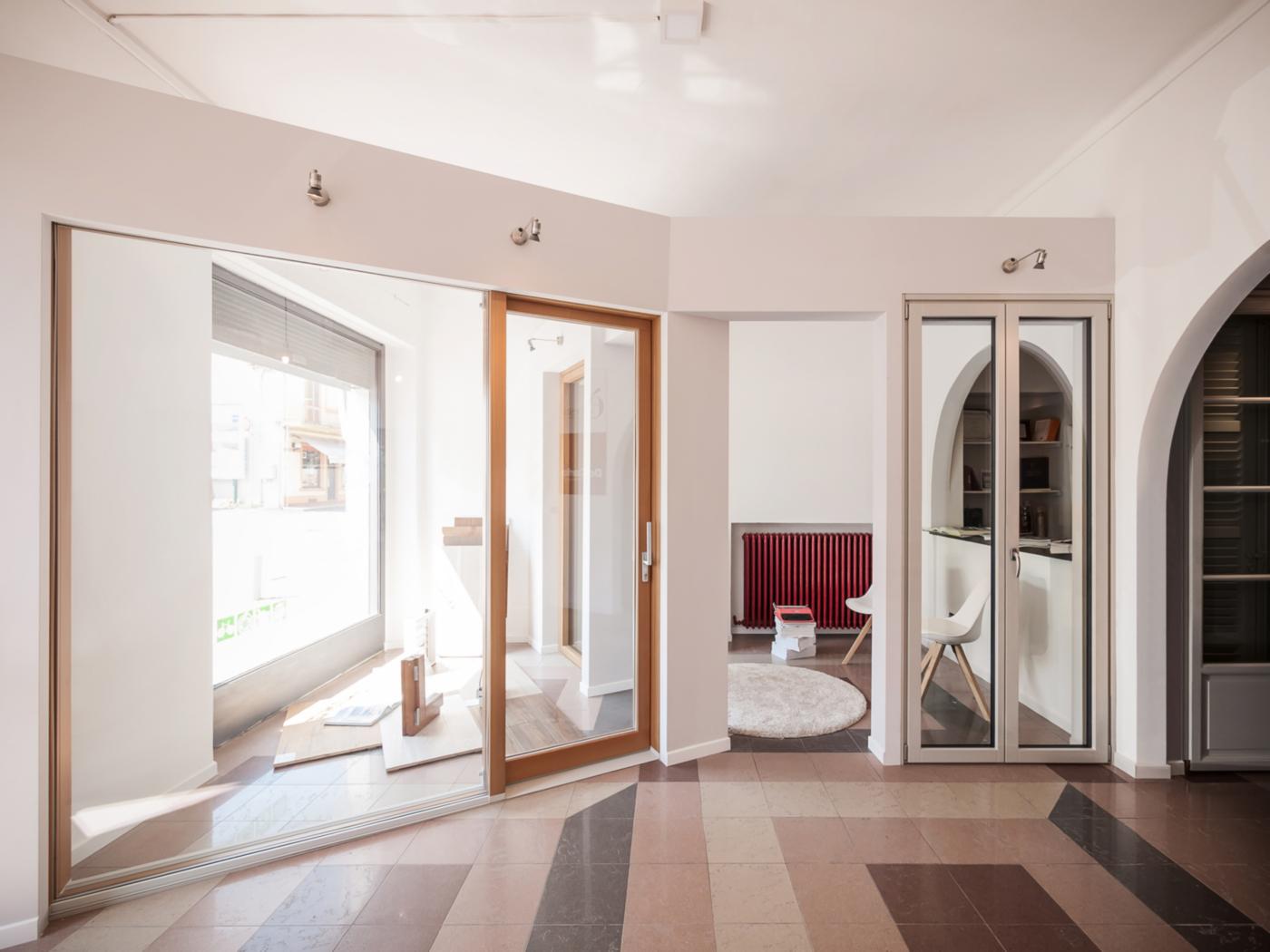 L'allestimento di un negozio di serramenti di alta gamma a Ivrea. Le pareti inclinate e la spina che danno dinamismo all'ambiente | Bottega di Architettura