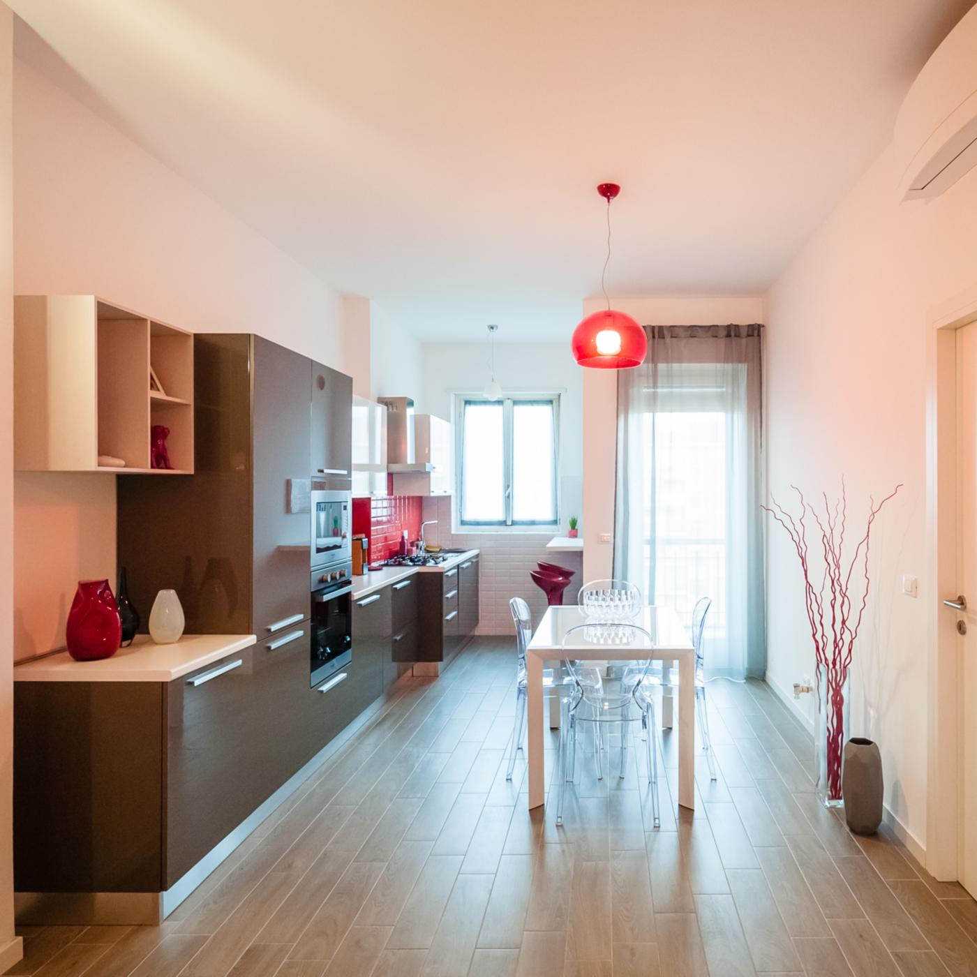 Una ristrutturazione che moltiplica gli spazi in un'appartamento degli anni '70. Il grande living, con tocchi rossi a creare un fil rouge | Bottega di Architettura