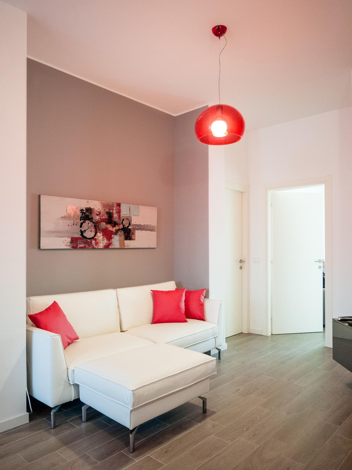Una ristrutturazione che moltiplica gli spazi in un'appartamento degli anni '70. La nuova zona salotto, ricavata nel cuore della casa, con tocchi rossi a creare un fil rouge | Bottega di Architettura