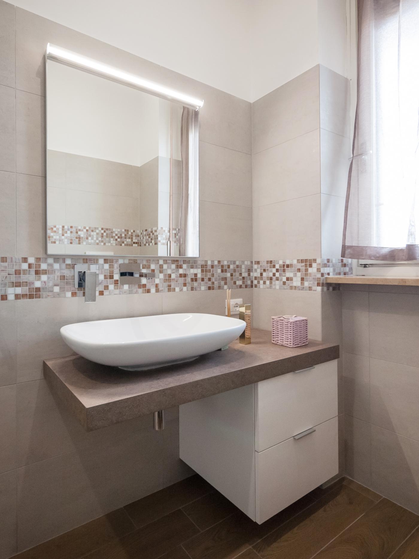 Una ristrutturazione che moltiplica gli spazi in un'appartamento degli anni '70. Il bagno tra piastrelle e mosaico, toni caldi e pavimento effetto legno | Bottega di Architettura