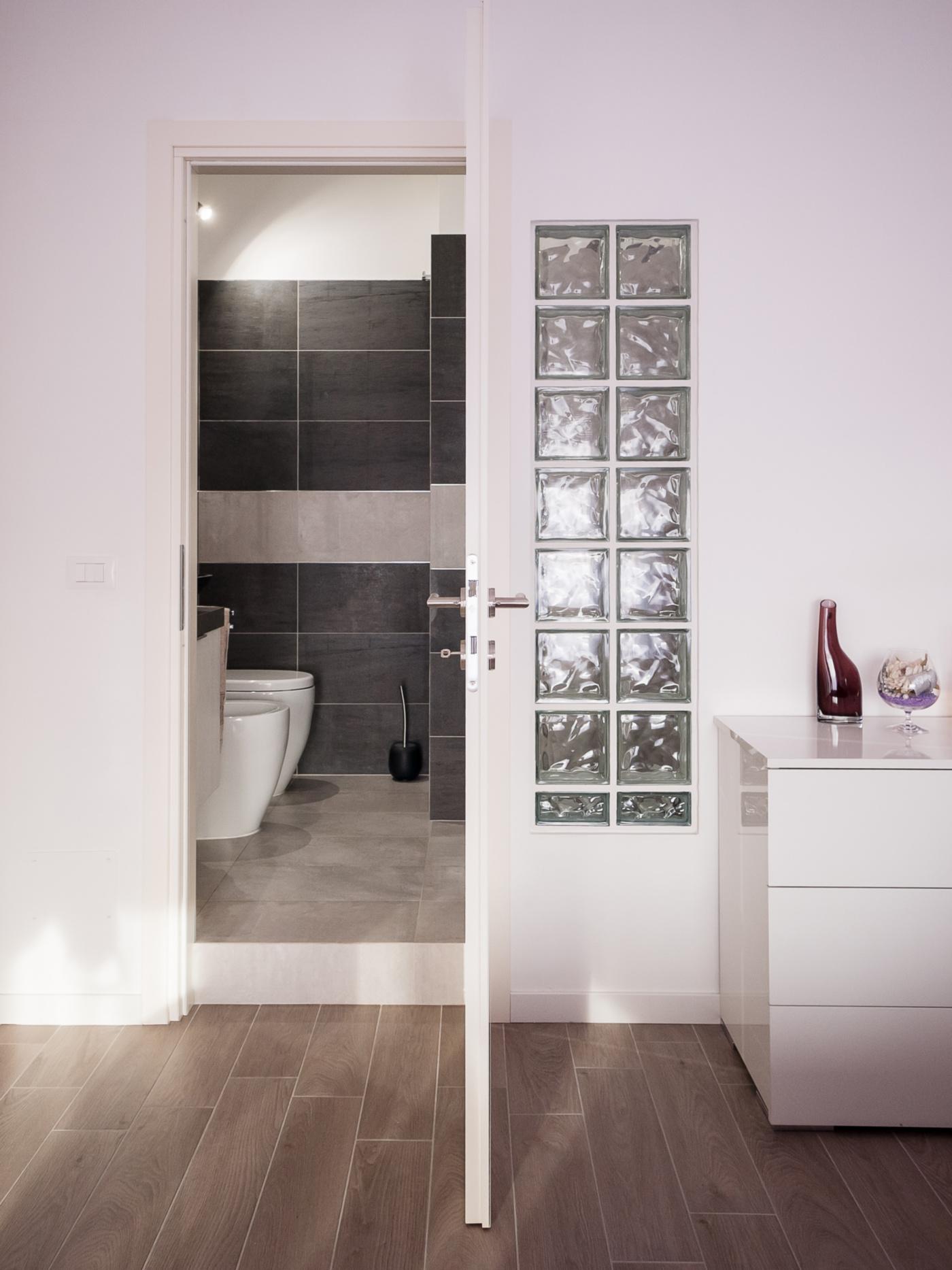 Una ristrutturazione che moltiplica gli spazi in un'appartamento degli anni '70. Il vetrocemento porta luce al bagno privato, con un tocco di seduzione | Bottega di Architettura