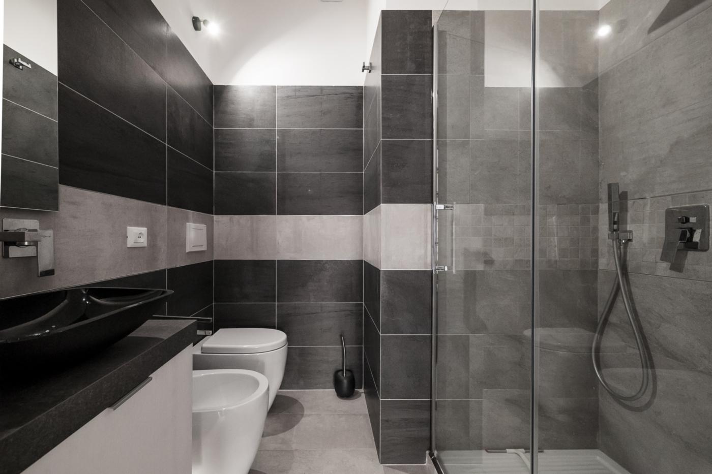 Una ristrutturazione che moltiplica gli spazi in un'appartamento degli anni '70. Il bagno della camera, con forti contrasti in bicromia | Bottega di Architettura