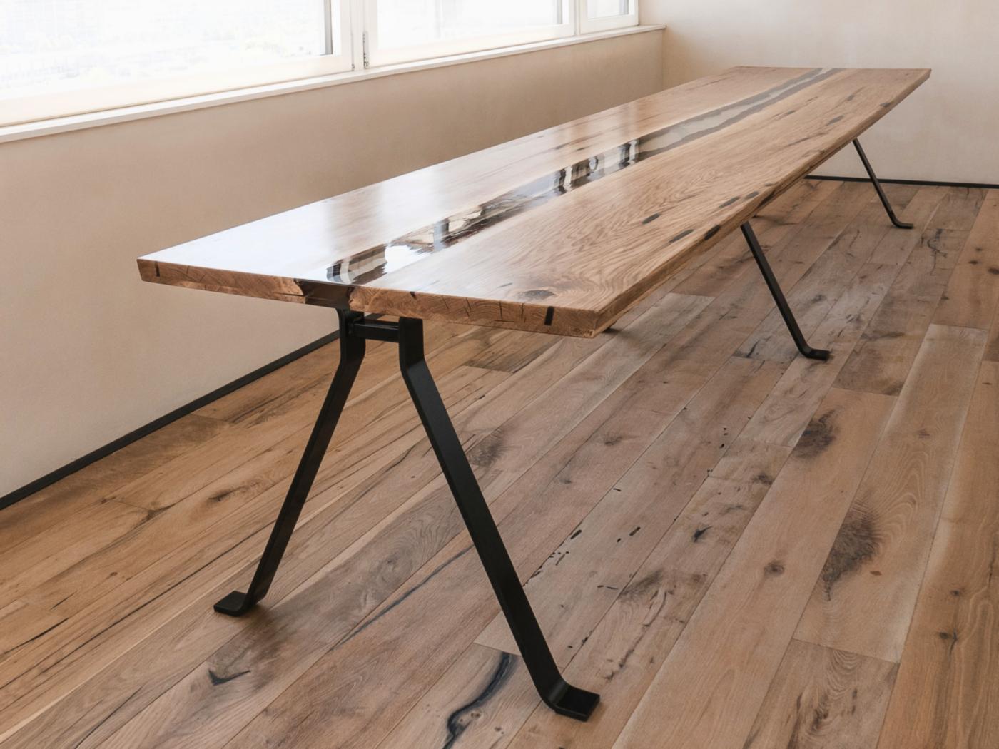 Un tavolo di design in rovere massiccio e resina, poetico e evocativo come un viaggio. Il tavolo si appoggia a tre gambe che omaggiano Enzo Mari | Bottega di Architettura