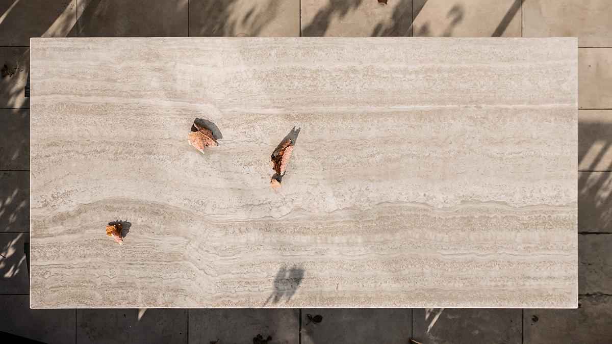DUCA è un tavolo composto da tre elementi: un piano di marmo, una linea ininterrotta di metallo, e una serie coordinata di dettagli a impreziosirlo. Un piccolo capolavoro disponibile su misura e in diverse varianti, coordinate, per interni e esterni | il piano di travertino | Bottega di Architettura | (c) Carlo Deregibus